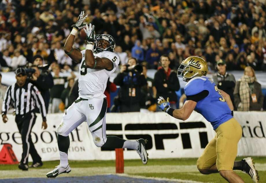 Baylor wide receiver and Midland High grad Antwan Goodley (5) hauls in an 8-yard touchdown pass after beating UCLA linebacker Jordan Zumwalt during the first half of the Holiday Bowl in San Diego. (AP Photo/Lenny Ignelzi) Photo: Lenny Ignelzi