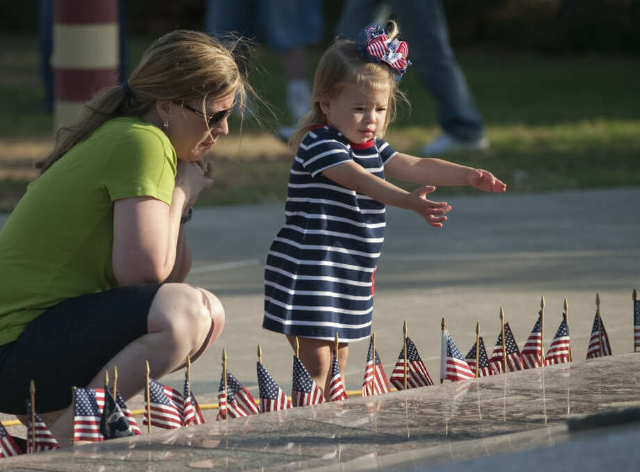 Micah Joy Kendrick, 2, and her mom, Candice, look at the flags put out Monday around the eternal flame memorial at the Permian Basin Vetnam Veterans Memorial before the Memorial Day ceremonies. Tim Fischer\Reporter-Telegram Photo: Tim Fischer