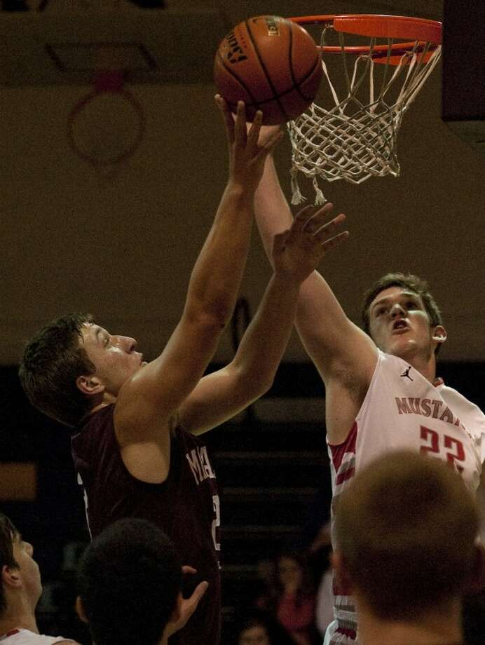 Midland Lee's Daniel Nelson lays in a basket as Houston Memorial's Graham Taylor tries to block his shot Friday during the second round of the Byron Johnston Holiday Classic game at Midland High gym. Tim Fischer\Reporter-Telegram Photo: Tim Fischer