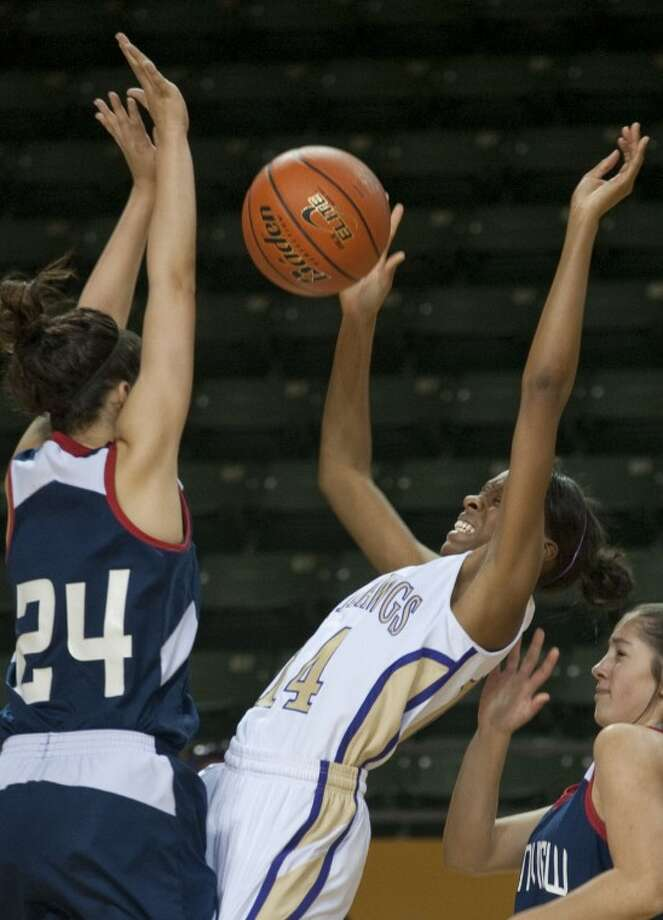 Midland High's Alexis Washington falls back mid shot as she is fouled by Plainview's Shalee Bennett Saturday in the 3rd place game of the Byron Johnston Holiday Classic at the Chaparral Center. Tim Fischer\Reporter-Telegram Photo: Tim Fischer