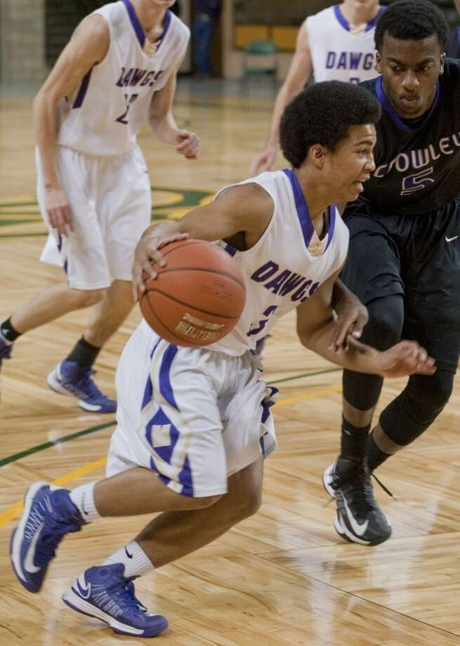 Midland High's Wesley Don Juan drives around Crowley's D'Myrian Robinson Saturday in the 3rd place game of the Byron Johnston Holiday Classic at the Chaparral Center. Tim Fischer\Reporter-Telegram Photo: Tim Fischer