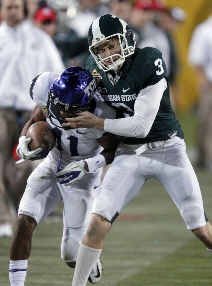 TCU punt returner Skye Dawson, left, is driven out of bounds by Michigan State punter Mike Sadler, right, during the second half of the Buffalo Wild Wings Bowl NCAA college football game Saturday, Dec. 29, 2012, in Tempe, Ariz. (AP Photo/Paul Connors) Photo: Paul Connors