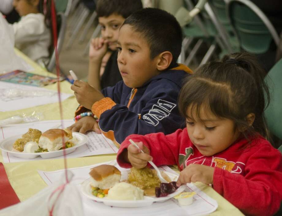 Larissa Marquez, 3, and her brother, Matthew, 6, enjoy turkey, stuffing and all the goodies Friday at the ninth Annual H-E-B Feast of Sharing at the Horseshoe. Photo by Tim Fischer/Midland Reporter-Telegram Photo: Tim Fischer