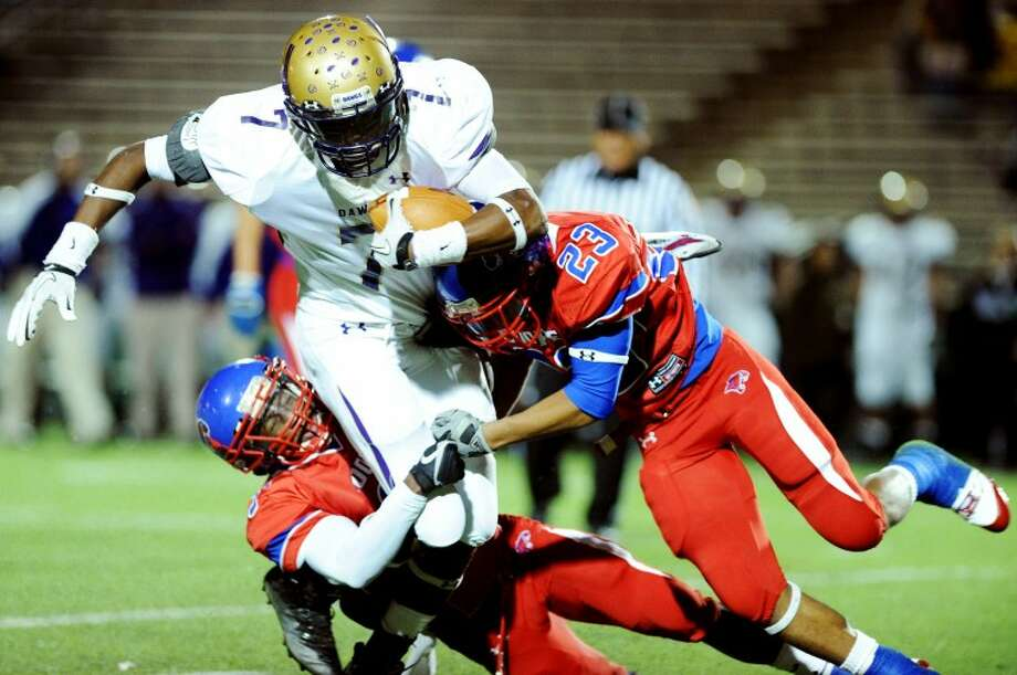 Joy Lewis/Reporter-News Midland's Donavon Lee is tackled by Cooper defensive back Fred Lawrence (3) and Cooper defensive back Mekiyah Brooks (23) during the first quarter of their game at Shotwell Stadium on Friday, November 4, 2011. Photo: Joy Lewis