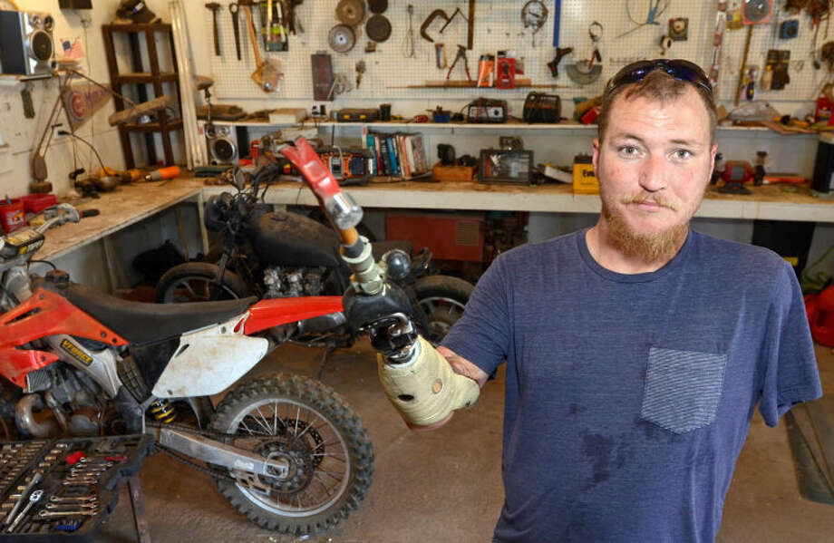 Midlander John Barfield works on four-wheelers and motorcycles despite losing both of his arms in an accident. James Durbin/Reporter-Telegram Photo: JAMES DURBIN