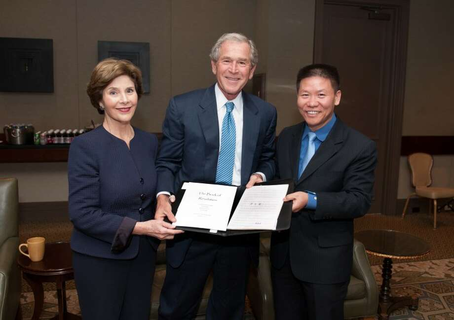 Bob Fu of China Aid Assoc. gives Pres. and Mrs. Bush hand copied bible pages by Chinese prisoners