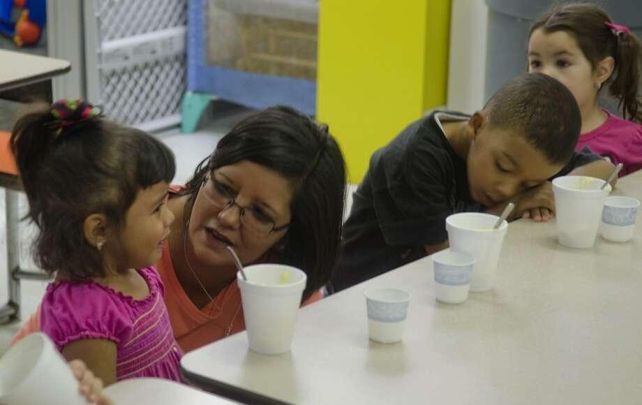 Clara Flores talks to one of her students at snack time Nov. 1 at Village School. Photo by Tim Fischer/Midland Reporter-Telegram Photo: Tim Fischer