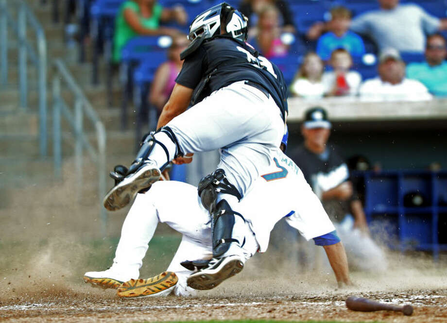 RockHounds' Dusty Coleman (7) collides with San Antonio catcher Eddy Rodriguez at home plate Wednesday at Citibank Ballpark. James Durbin/Reporter-Telegram Photo: JAMES DURBIN