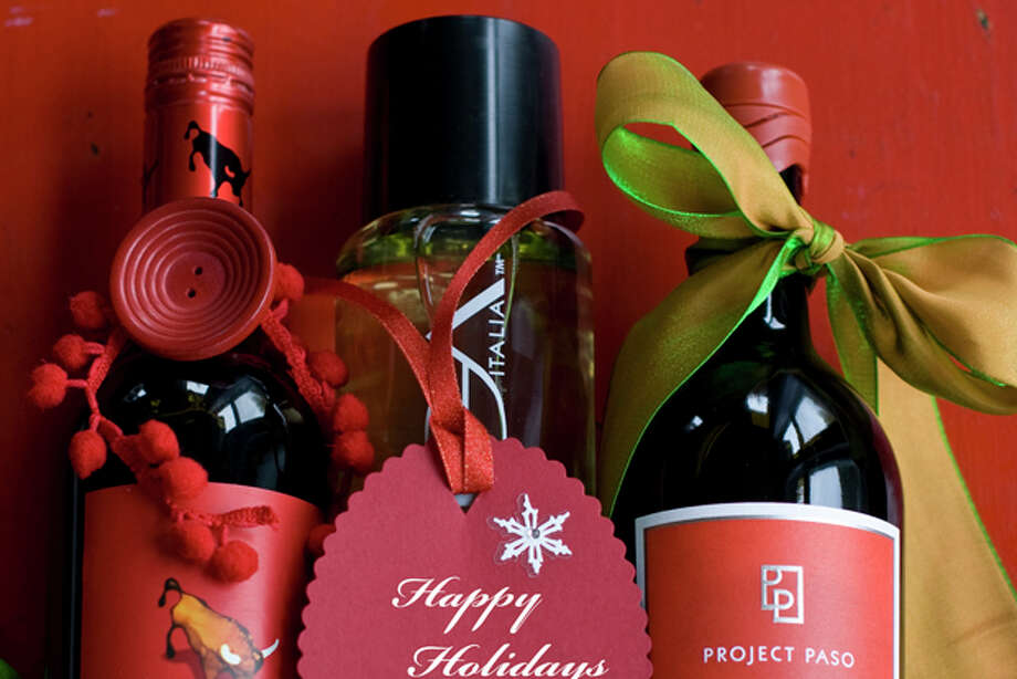 This Oct. 26, 2011 photo shows, from left to right, Tempra Tantrum cabernet, Voga pinot grigio and Project Paso zinfandel wine in Concord, N.H. Trendy, tasty and one-size-fits-all, wine is a versatile holiday gift. (AP Photo/Matthew Mead) Photo: Matthew Mead / FR170582 AP