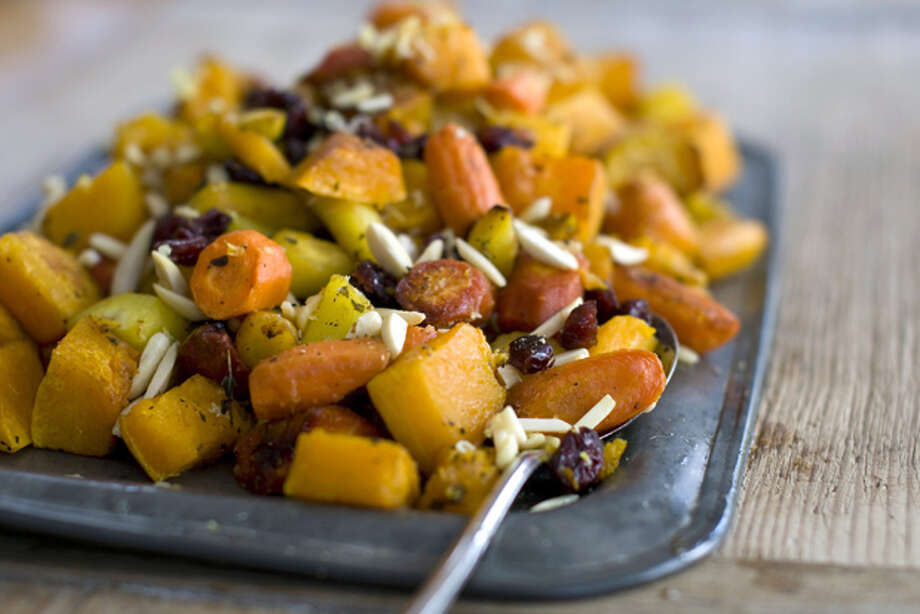 This Oct. 17, 2011 photo shows roasted squash with almonds and cranberries in Concord, N.H. This dish is nutty, crunchy, roasted, sweet and savory. (AP Photo/Matthew Mead) Photo: Matthew Mead / FR170582 AP