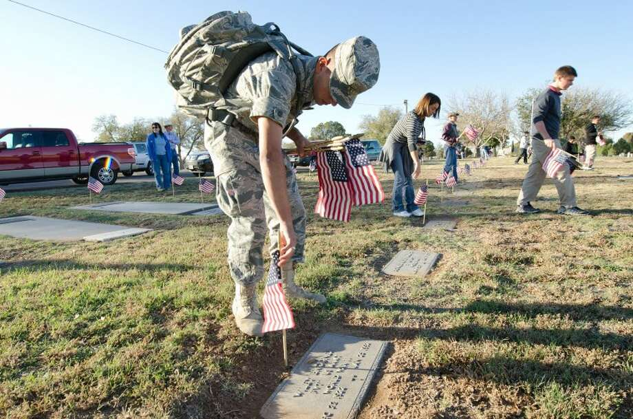 Lee High School JROTC Cadet Master Sgt. Abel Bravo places a flags onto veterans' graves Thursday at Fairview Cemetery. Cindeka Nealy/Reporter-Telegram Photo: Cindeka Nealy