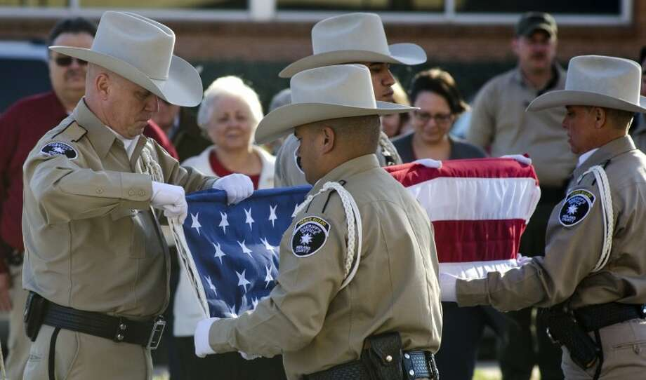 Midland Sheriff Department Honor Guard members, Ofc. Robert Stephenson, Ofc. Israel Ramirez, Sgt, Herb Fernandez and Sgt. Lori Fuson fold the American Flag that has been flying outside the Midland County Courthouse during a ceremony Wednesday afternoon to drape Judge Hyde's casket today for services. Photo by Tim Fischer/Midland Reporter-Telegram Photo: Tim Fischer