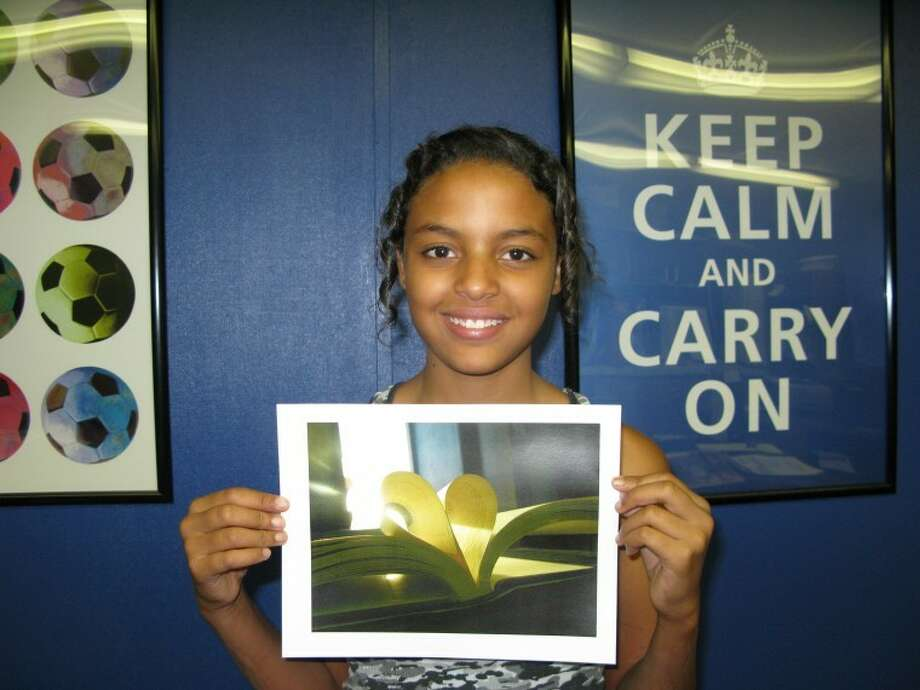 "Taezja Bell, 12, is a regional winner in the Boys & Girls Club photography contest for her photo titled ""My Love for Books."" She will advance to the national competition. Photo: Courtesy Photo"