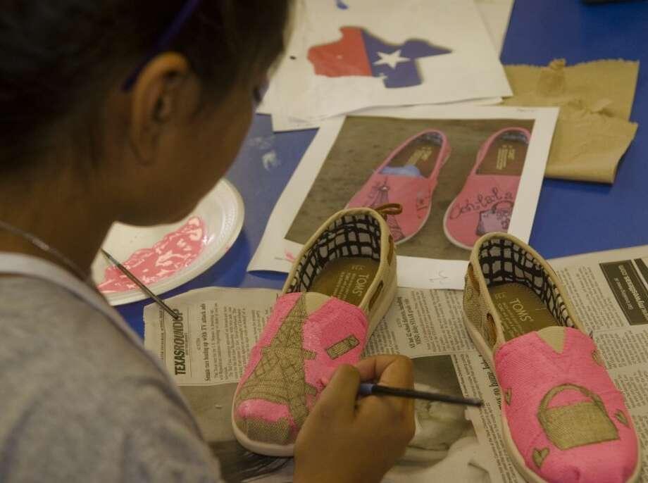 Julissa Carrasco, 12, paints a pair of TOMS Tuesday at a summer art class at Trinity School. Photo: Tim Fischer/Reporter-Telegram