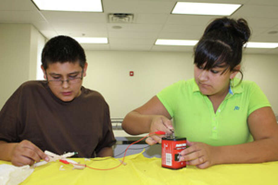 Early College High School sophomores Joseph Hernandez and Cecilia Delhierro test whether their coil gun will launch a magnet when plugged into an electrical current Wednesday at Midland College during the Summer Math Academy in partnership with Texas Tech University. Photo: Meredith Moriak/Reporter-Telegram