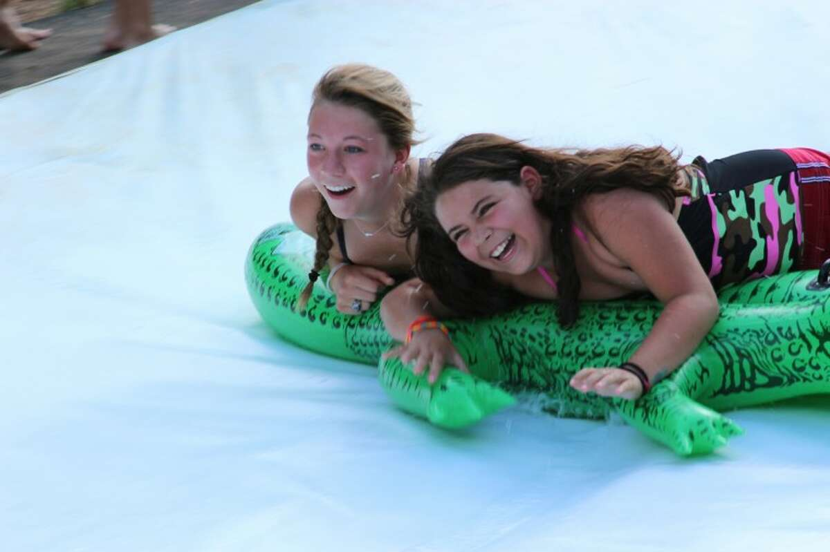 Op Camp counselor Olivia Fryt and camper McKenzie Millican go down the slide July 3 at Butman Methodist Camp and Retreat Center.