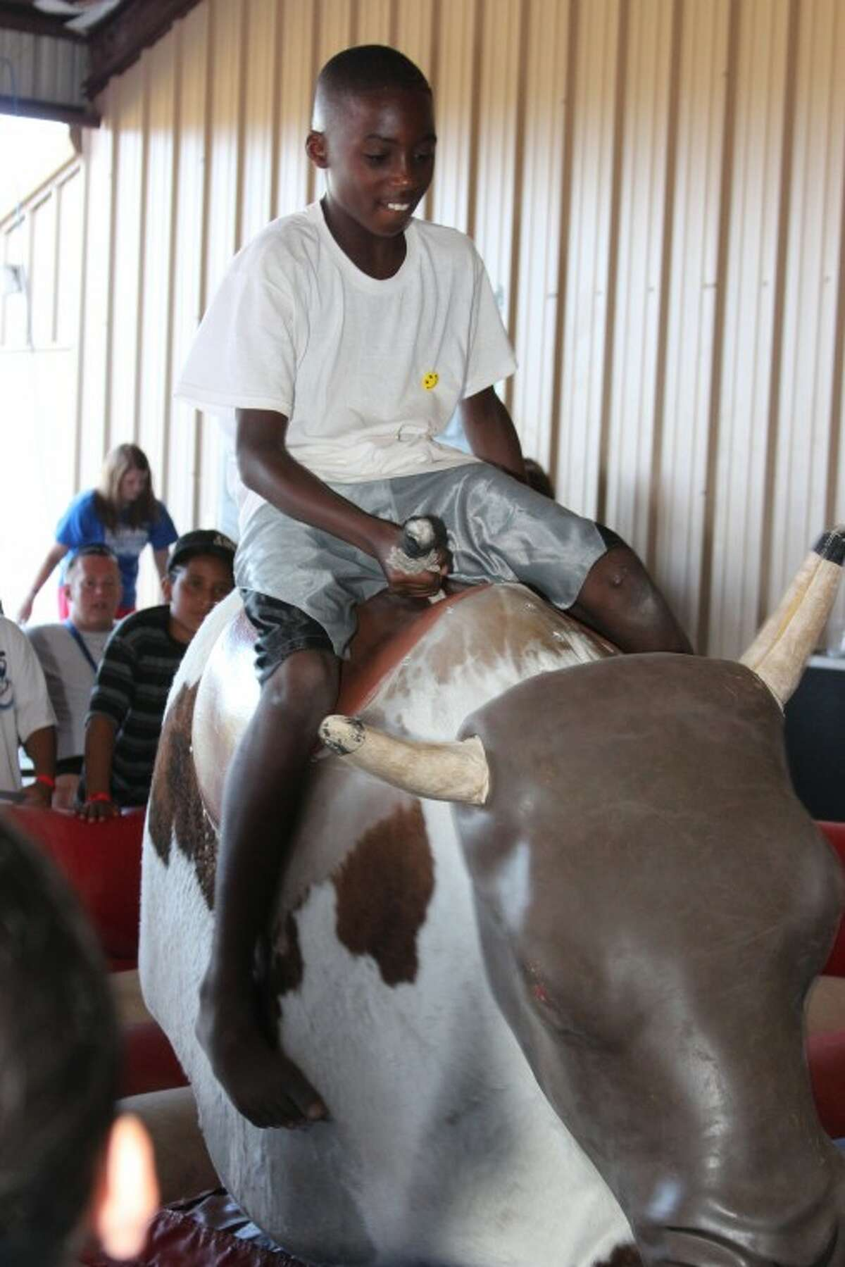 """Midlander Devin Harris rides a mechanical bull July 3 at Opportunity Camp. The bull and other inflatables were brought to camp for the infamous """"Jumper Night."""""""