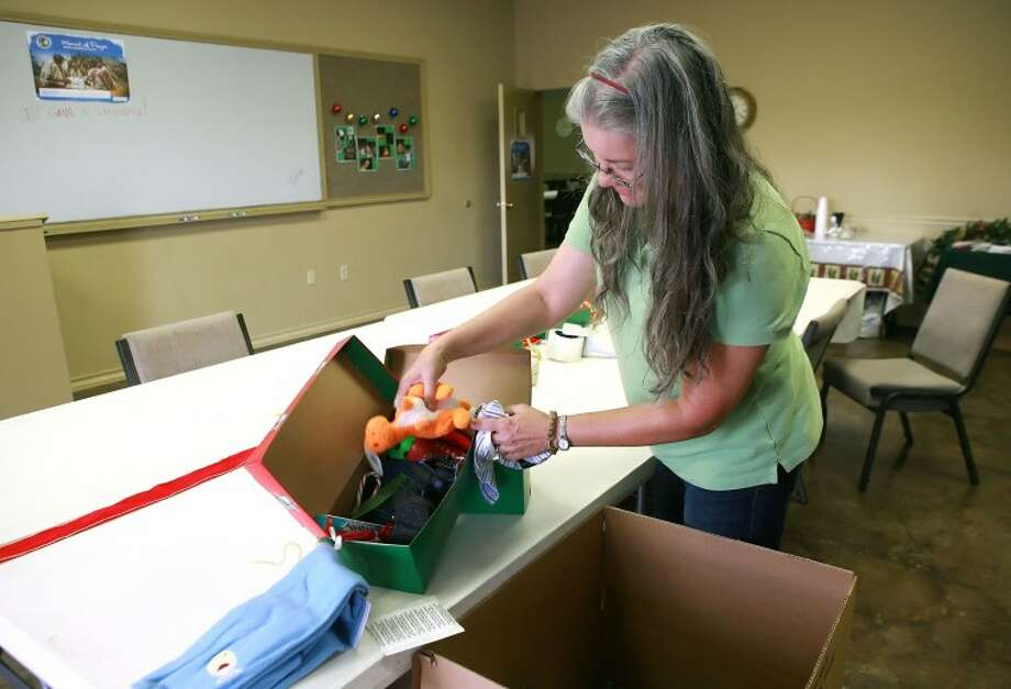 Emily Yoxsimer looks at some of the items in an Operation Christmas Child Shoe Box, Monday at Midland Bible Church. Midland Bible Church is among the 3,300 drop-off sites around the country who are collecting shoe boxes filled with toys, clothes, and other items for children overseas. Cindeka Nealy/Reporter-Telegram Photo: Cindeka Nealy