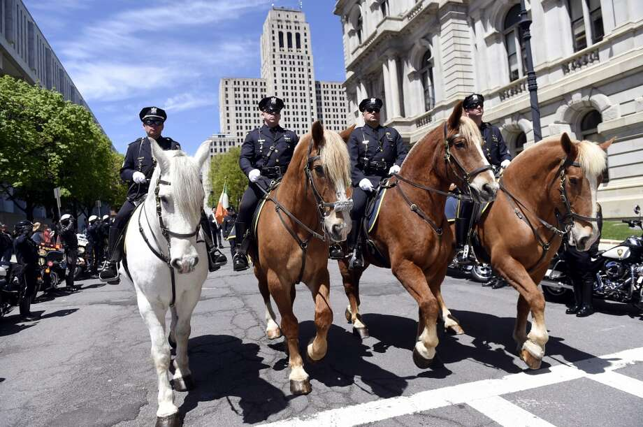 Albany Police Officers ride their mounts past the Capitol on State Street as part of a remembrance ceremony to honor fallen comrades at the State of New York Police Officers Memorial on Tuesday, May 10, 2016, in Albany, N.Y. (Cindy Schultz / Times Union) Photo: Albany Times Union