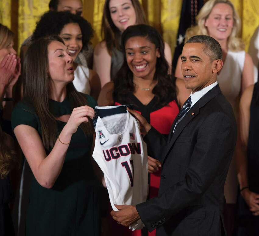 US President Barack Obama holds a women's jersey as he poses with player Breanna Stewart at the White House in Washington, DC, May 10, 2016, during an event welcoming the 2016 NCAA Champion UConn Huskies women's basketball team.