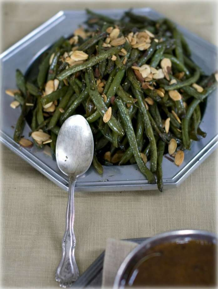 This Oct. 17, 2011 photo shows oven-candied green beans amandine in Concord, N.H. This recipe can be taken a step further by topping the green beans with chopped cooked bacon. (AP Photo/Matthew Mead) Photo: Matthew Mead
