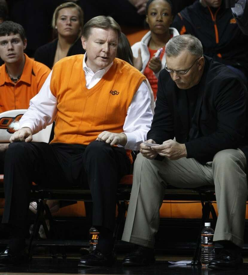 In this Nov. 9, 2011, photo, Oklahoma State head coach Kurt Budke, left, sits on the bench next to associate head coach Jim Littell, right, during an exhibition college basketball game against Ft Hays State in Stillwater, Okla. Following the deaths of Budke and assistant Miranda Serna, Littell will assume head coaching responsibilities. (AP Photo/Sue Ogrocki) Photo: Sue Ogrocki