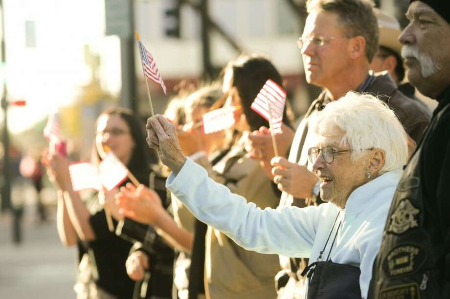 Betty Reimers waves her American flag as some of the 25 injured soldiers and their wives pass through downtown Midland Thursday during the Hunt for Heroes Parade. Photo: Cindeka Nealy/Reporter-Telegram