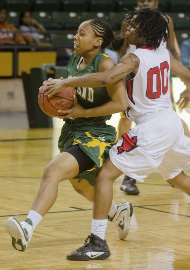 Trinity Valley's Breanna Lewis gets a hand on the ball as Midland College's Kamilah Carter drivs to the basket Saturday night in the championship game of Midland College Women's National Invitational Tournament. Photo by Tim Fischer/Midland Reporter-Telegram Photo: Tim Fischer