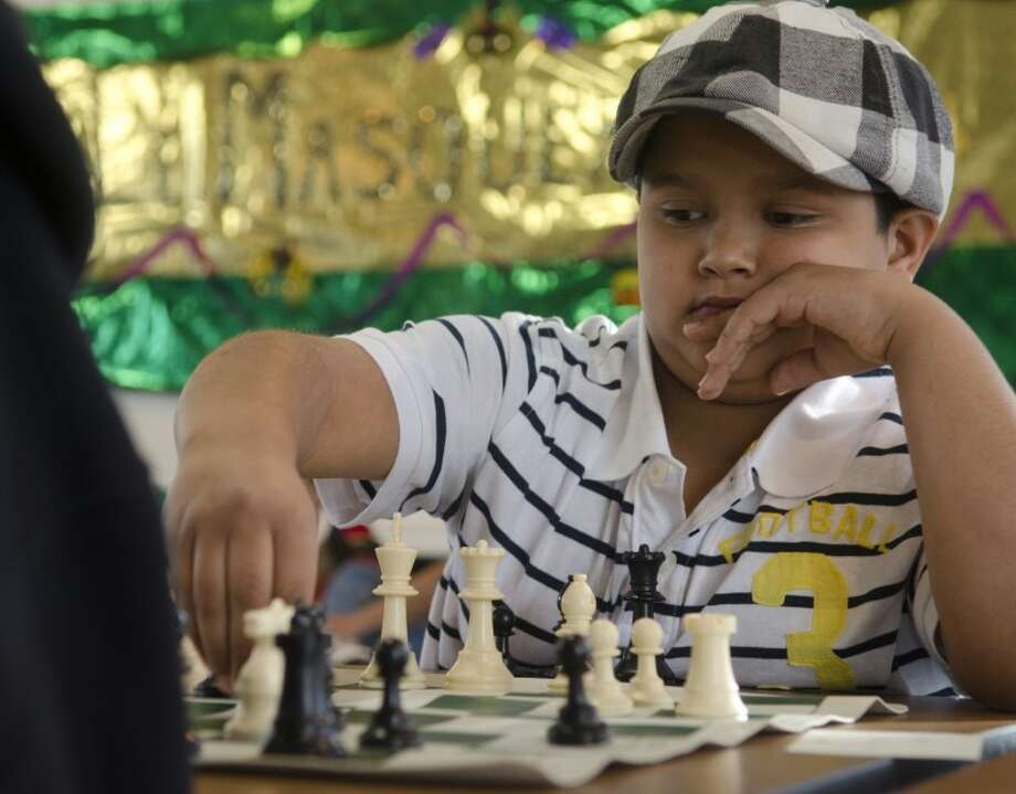 Nathaniel Kuhn, 10, from Abilene, holds onto his piece as he examines the board before letting go during a match at the K-12 West Texas Chess Tournament Saturday morning at Trinity School. Photo by Tim Fischer/Midland Reporter-Telegram Photo: Tim Fischer