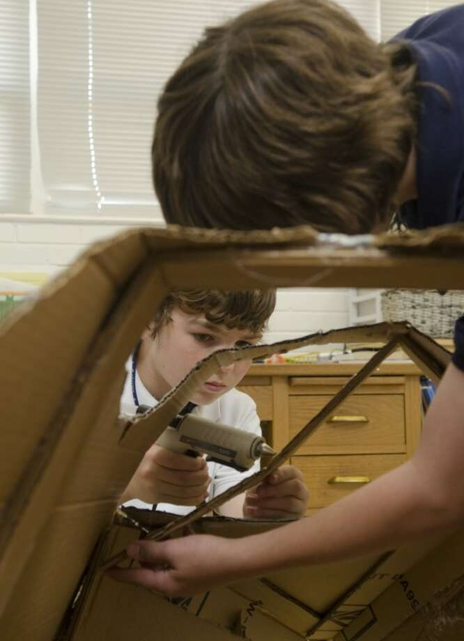 David Purdy hot glues a support piece to the rocket as Will Powell holds it Moday duirng work on their project with Destination Imagination at Carver Center. Photo by Tim Fischer/Midland Reporter-Telegram Photo: Tim Fischer