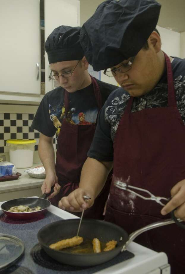 Lee seniors, Lalo Rubio takes the temperature of his pork as Sean Kator sautes mushrooms as they practice making mushroon pork scaloppini Wednesday in culinary class. They and five other LHS students will be competing in the state culinary compitition in Dallas. Photo by Tim Fischer/Midland Reporter-Telegram Photo: Tim Fischer