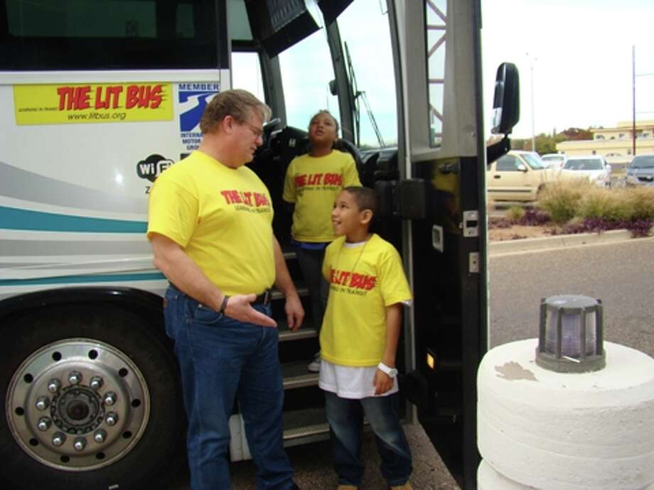 Bill Griffin, left, of Learning in Transit, stands in front of the Lit Bus with Devin and Alenia after a Big Brothers Big Sisters trip to the Science Spectrum in Lubbock. Learning in Transit is a nonprofit organization that aims to supplement students' academic experience with travel. Photo: Courtesy Photo