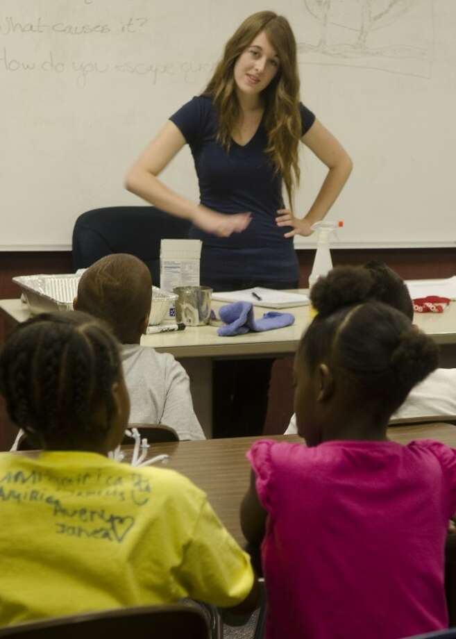 Southwestern University student Michelle Moses, a 2010 Lee graduate, volunteered to teach a three-week science course at Casa de Amigos. Monday Moses was teaching about quicksand and asked students what they thought it was made of. Photo: Tim Fischer/Reporter-Telegram
