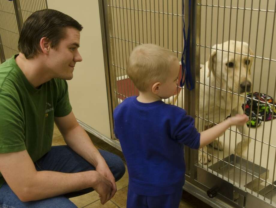 Scott Lynch and his two-year-old son Landon, look at dogs at the PetSmart Adoption Center Saturday afternoon. Photo by Tim Fischer/Midland Reporter-Telegram Photo: Tim Fischer