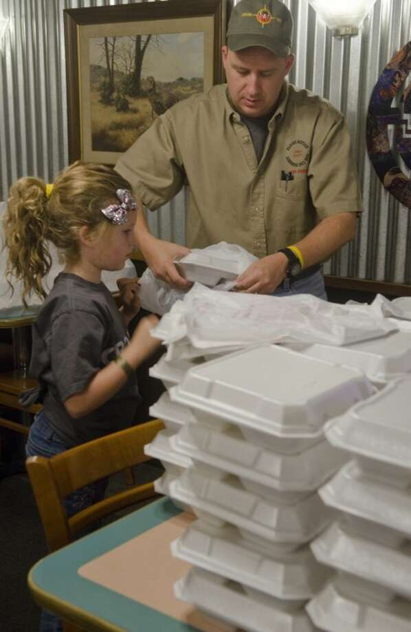 Abby Fivecoat helps her father, Ray Fivecoat, chief-elect of the Plains Nation tribe, and other YMCA Indian princesses pack Thanksgiving meals that were delivered Thursday morning. Photo: Tim Fischer/Reporter-Telegram