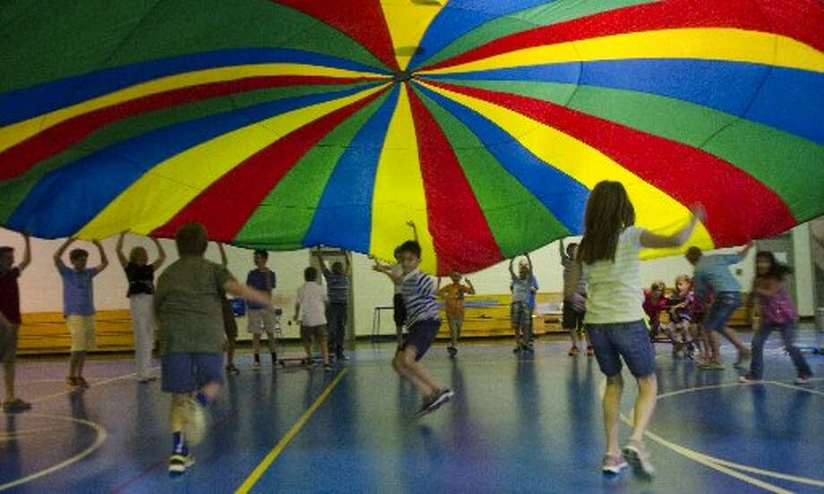 Trinity fifth graders play parachute Thursday with Bynum School students during their weekly interactive gym class at Trinity. Photo: Tim Fischer/Midland Reporter-Telegram