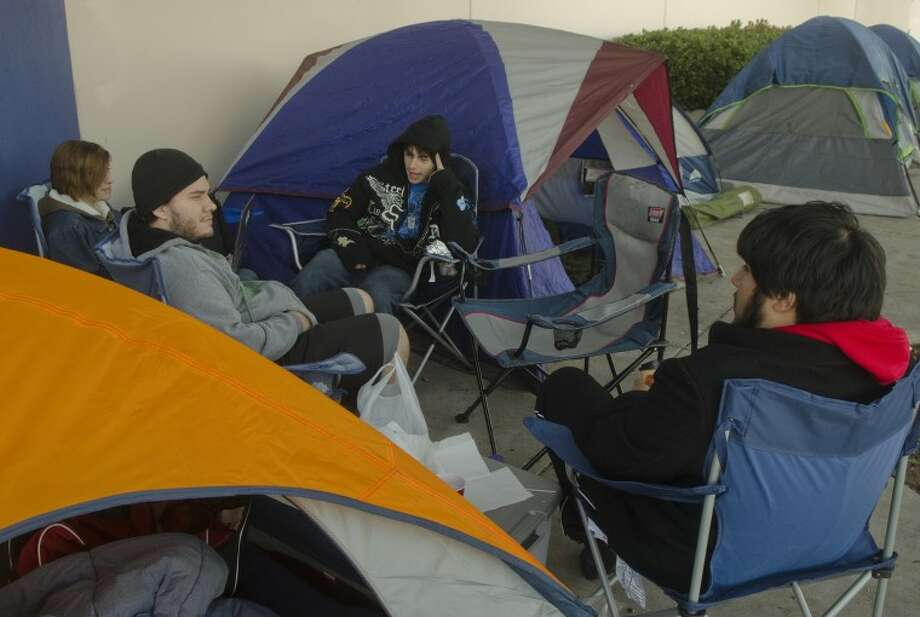 Chris Gonzalez, April Van Zandt, left, Kyle Becker and Javier Silva, right, talk Wednesday morning as they pass the time outside Best Buy waiting to get door buster deals on TVs on Black Friday. Photo: Tim Fischer/Reporter-Telegram