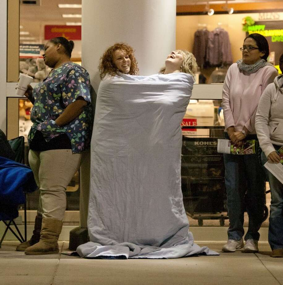Kristina Soliz, left, and her mother, Karla Hiers, share a blanket to keep warm Thursday evening as they wait for Kohl's 7 a.m. opening. Photo: Cindeka Nealy/Reporter-Telegram