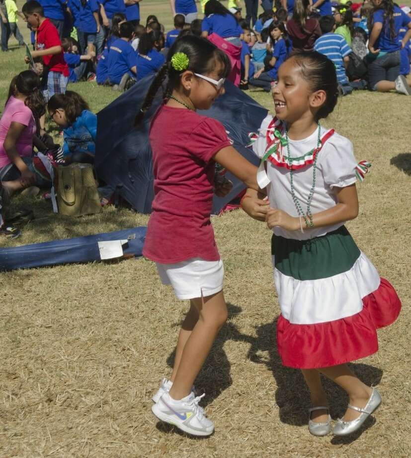 Desiree Chavev, in red, and Martinza Munoz, first-graders at Henderson Elementary, dance on the grass outside the Midland Hispanic Cultural Center during the Cinco de Mayo celebration. Photo: Tim Fischer/Reporter-Telegram