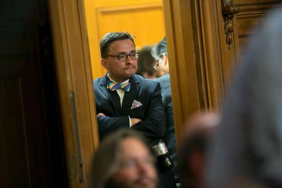 Board of Supervisors member David Campos heads into the hallway for recess after the meeting is interrupted by protesters at City Hall on Tuesday, May 10, 2016 in San Francisco, Calif. The recess lasted a few minutes after sheriff's deputies removed the protesters.