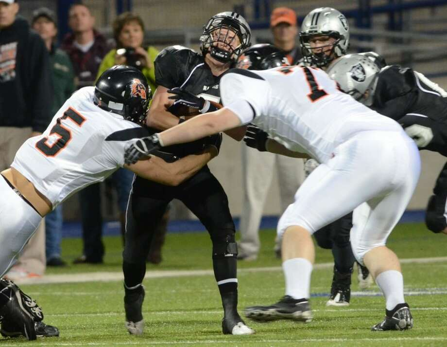 Aledo's Dayne Davis (5) and Ryan Dawsey (77) put a hit on Canyon receiver Logan Brittain (5) Friday during their Class 4A Division II playoff game at Grande Communications Stadium in Midland. Cindeka Nealy/Reporter-Telegram Photo: Cindeka Nealy