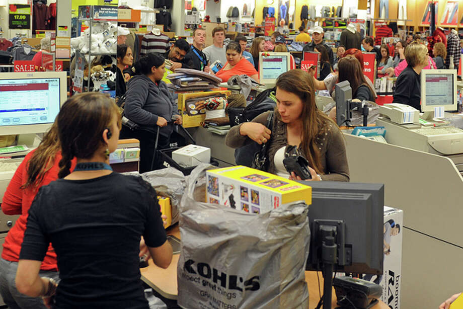 Customers check out at Kohl's in Wichita Falls, Texas as lines wrapped around the store on both sides and back down the center aisles by 1:30 a.m. Kohl's opened at midnight for Black Friday, along with other retail stores such as Best Buy. (AP Photo/Wichita Falls Times Record News, Patrick Johnston) Photo: Patrick Johnston / Wichita Falls Times Record News