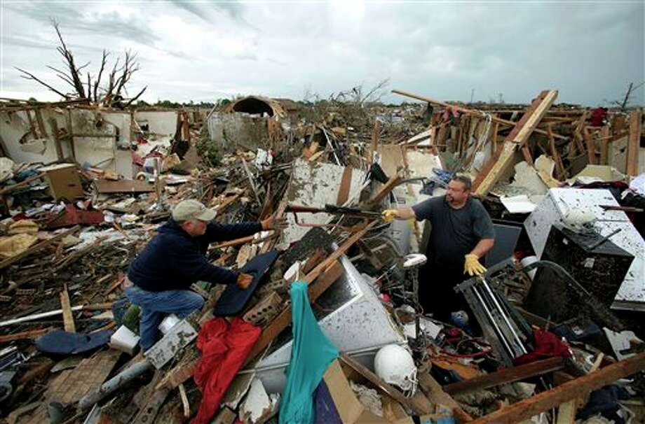 Dalton Sprading, right, hands a gun to his uncle Roger Craft as he salvages items from his tornado-ravaged home Tuesday, May 21, 2013, in Moore, Okla. A huge tornado roared through the Oklahoma City suburb Monday, flattening an entire neighborhoods and destroying an elementary school with a direct blow as children and teachers huddled against winds. (AP Photo/Charlie Riedel) Photo: Charlie Riedel / AP2013