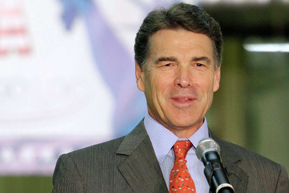 Republican presidential candidate, Texas Gov. Rick Perry talks to employees at Logo Loc during a campaign stop, Tuesday, Nov. 29, 2011, in Manchester, N.H. (AP Photo/Jim Cole) Photo: Jim Cole / AP