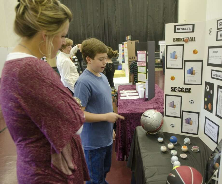 Hayden Johnson, fifth-grader at Hillander, describes his science fair project, Sport Ball Rebounds, to Karen Fisher in November at Hillander. Photo: Tim Fischer/Reporter-Telegram