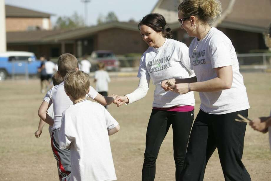 Mary Higby, left, and Kristi Hendricks hand students popsicle sticks after each quarter-mile earlier this month during a Fannin Elementary Running Club training session.  Photo: Cindeka Nealy/Reporter-Telegram