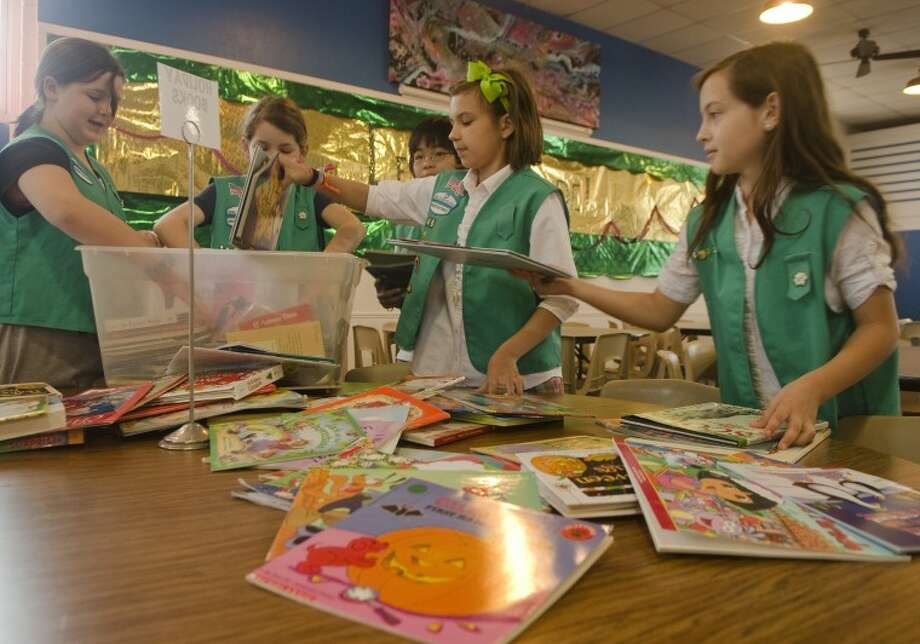 Members of Girl Scout Troop 46 at Trinity School sort donated books as they prepare for a book sale Saturday at Trinity to benefit Bynum School. Photo: Tim Fischer/Reporter-Telegram