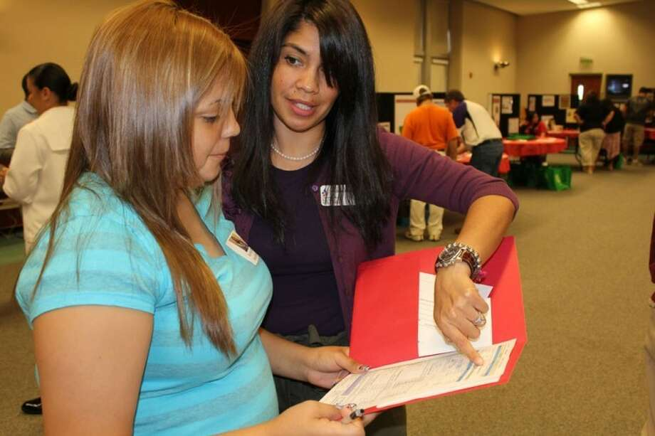 Midland High School Communities in Schools representative Andrea Morales goes over a budget with MHS junior Karina Salazar Saturday during a budgeting and financial literacy workshop at First Presbyterian Church. Though she had a college degree and steady job as a bank manager, Salazar's budget was still tight and required her to take EZ-Rider rather than have a car.
