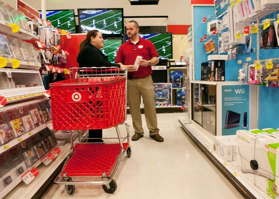 Dan Gilbert assists Rosie Enriquez with choosing the right accessories to go with the Nintendo Wii game console Monday at Target. Cindeka Nealy/Reporter-Telegram Photo: Cindeka Nealy
