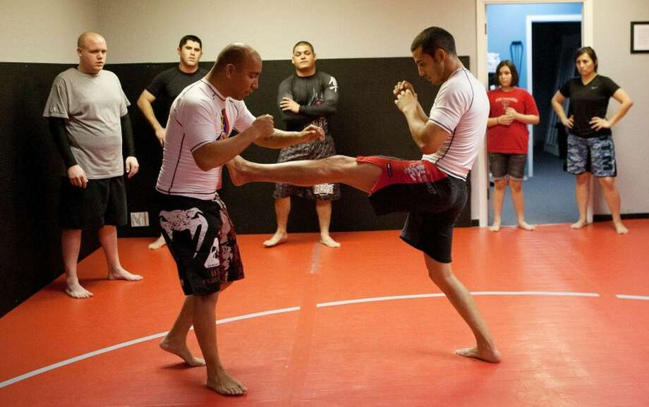 "Instructor Victor Hernandez, left, and Justin Campos demonstrate a ""front tip,"" which is a move used to knock an opponent off balance, Nov. 22, at Rhino BJJ. Cindeka Nealy/Reporter-Telegram Photo: Cindeka Nealy"